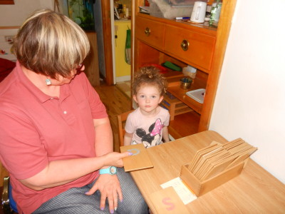 A young friend practices her letter sounds with a teacher.