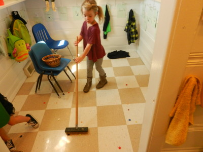 Children practice how to sweep the floor so when something is spilled they can clean up without assistance.