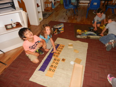 Two children often work together to count to 100 using the tens board.