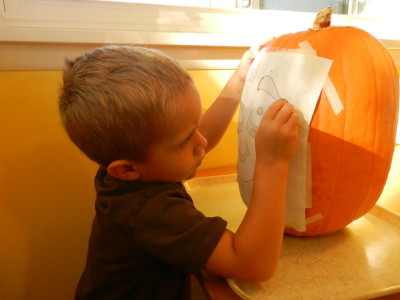 Using a push pin, we mark our pumpkin to carve into a jack-o-lantern.