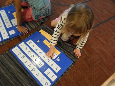 Self-correcting step boards aid a child in matching letter symbols.
